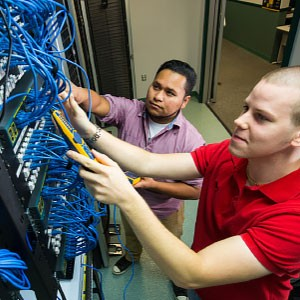 Information Technology and Networking program students work in server room.