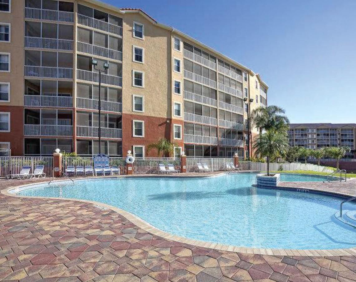 Condominium with balconies overlooking outdoor pool.
