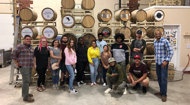 A group of Delaware Tech students standing with the owners of Painted Stave Distilling in front of a large quantity of barrels