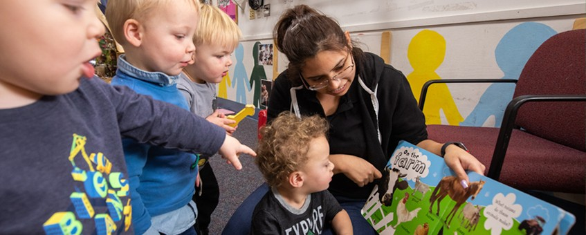 A Paraeducator student reading a picture book with four young children