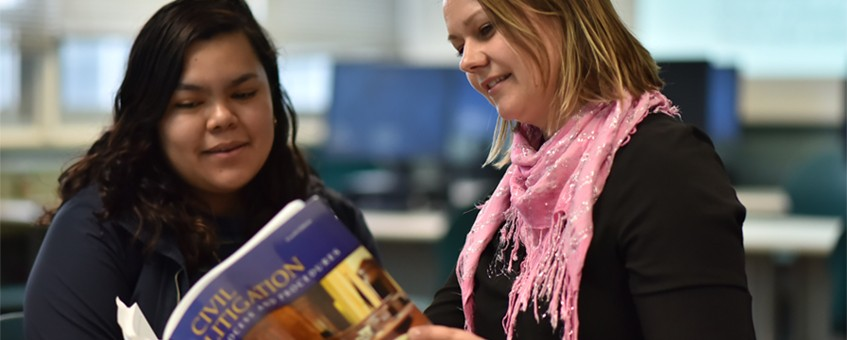 Two students in a Paralegal class looking at a Civil Litigation textbook