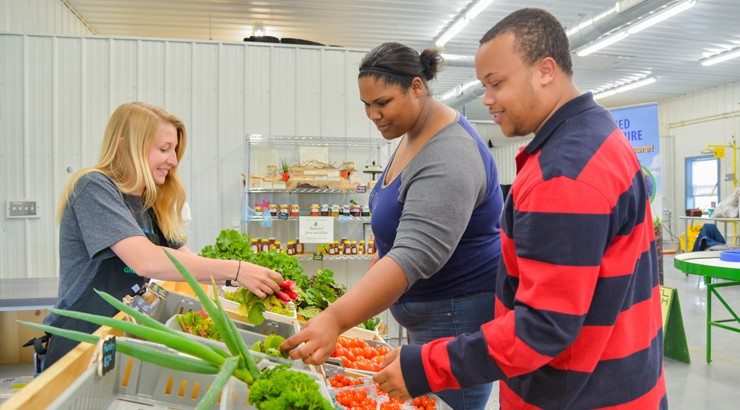 Courtney Bowski assisting Stephanie Showell and Justin Taylor at the farm market