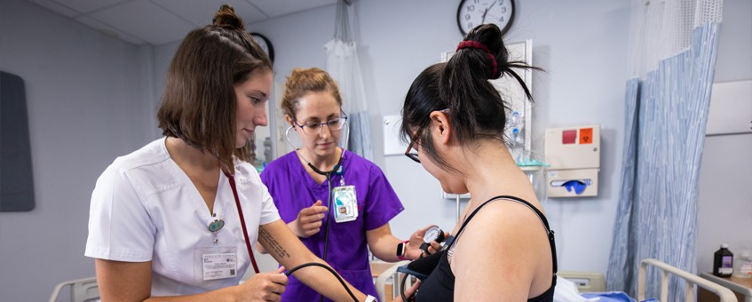 A nursing instructor demonstrates a medical principle on a volunteer alongside a student
