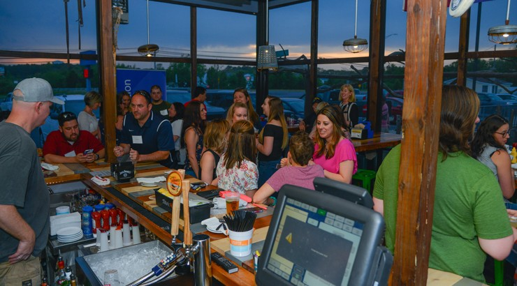 Delaware Tech alumni reconnect with former classmates and instructors at the reserved porch bar at the Crooked Hammock