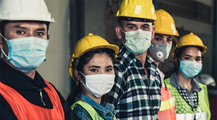 A line of people looking at the camera, all wearing hard hats, work clothes, safety vests, and surgical face masks to protect from airborne pathogens