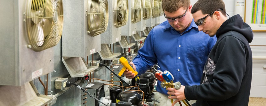 Two HVAC students interpret information from the equipment in their class