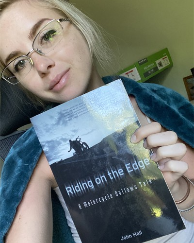 Summer Klair holding up Riding the Edge by John Hall