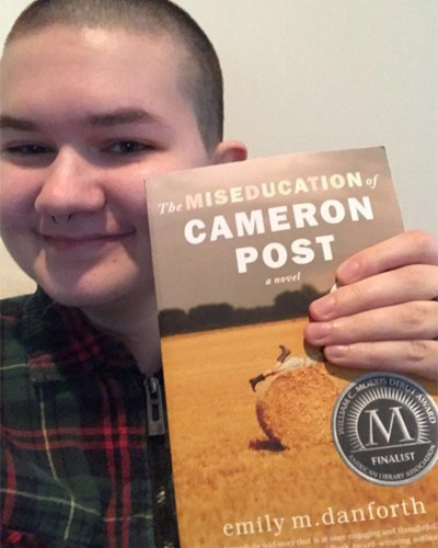 Aubrey Reed-Roland holding up The Miseducation of Cameron Post by Emily M. Danforth