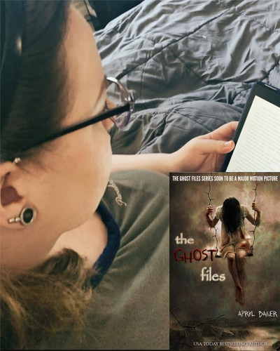 Sarah Stapleford reading The Ghost Files by Apryl Baker on a tablet