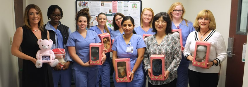 Rivera (with pink My Baby's Heartbeat Bear) stands with current sonography students and faculty.