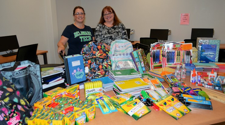 Cynthia Larson and Tammy Fenimore beside a table full of school supplies