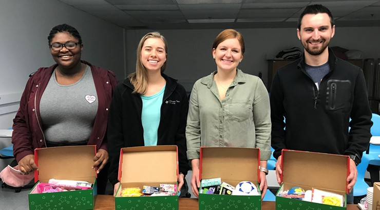 Lanaya Smith, Abigail Andrews, Hannah Snyder, and Gavin Brown holding shoe boxes full of toys