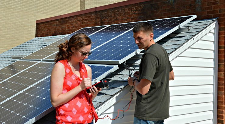 Two solar students work on a solar panel