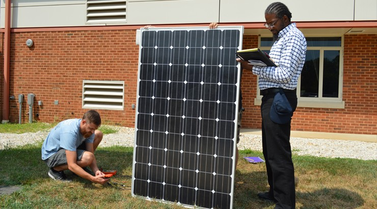 Mike Milspaw takes current measurements from a solar panel while Newton Rennie records the measurements