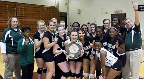 Coach Cindy Savage (back row center) and her champion Lady Hawks volleyball team, pictured with Assistant Coach Marc Laslow (far right standing) and Support Staff Kristine Ingram (far left standing).