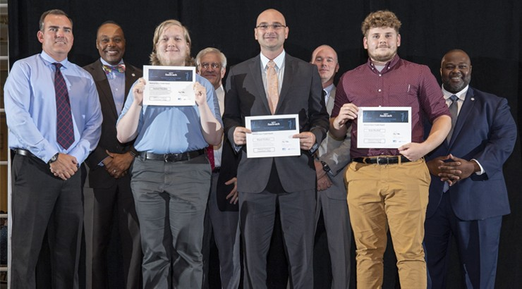 A group of students standing in a line holding up their awards