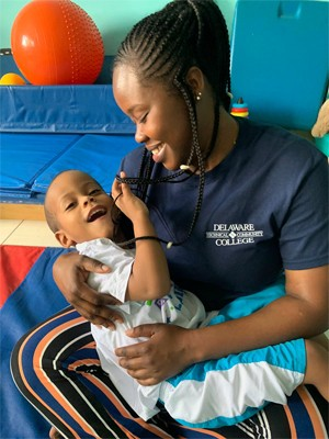 A nursing student wearing a Delaware Tech t shirt holding a young boy and smiling