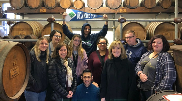 A group of students and instructors in a group surrounded by barrels with one student holding up a Delaware Tech banner