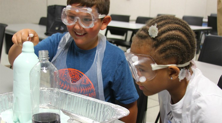 Two summer camp students doing a science experiment and wearing goggles