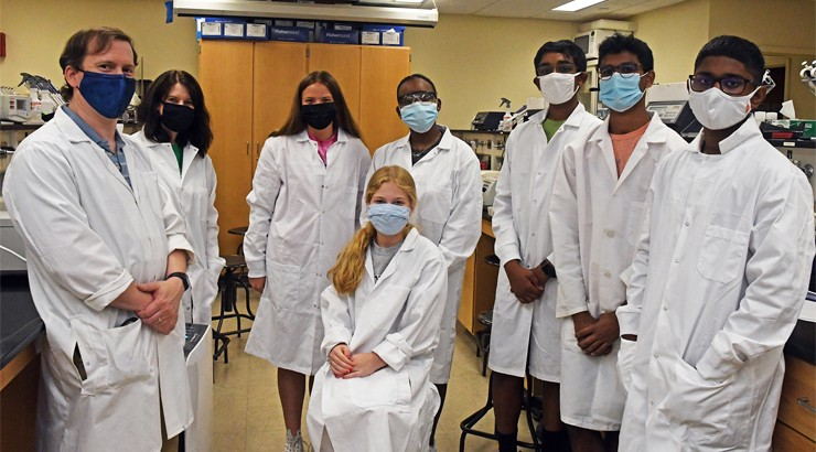 A group of students in lab coats and face coverings standing together with their instructor