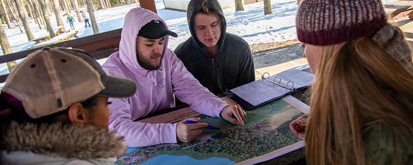 Four students sitting at a picnic table looking at the map of a state park