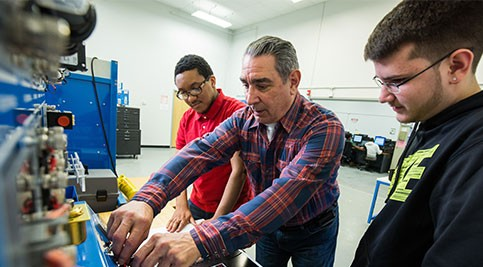 Khory Bivens and Shawn Davis, both 11th graders at William Penn High School, work with instructor J. Robert Blyman on electromechanical training equipment.