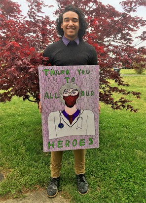 Wellington Rosario holding a poster he made that says Thank You To All Our Heroes