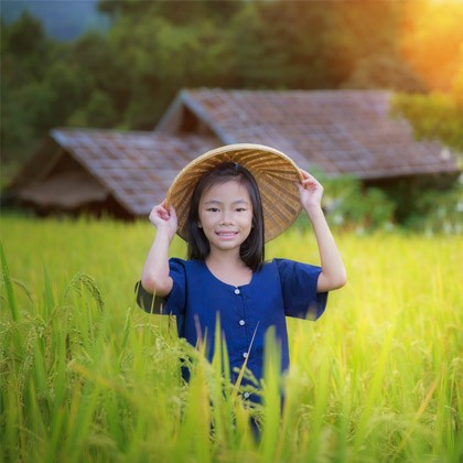 Vietnamese girl standing in field.