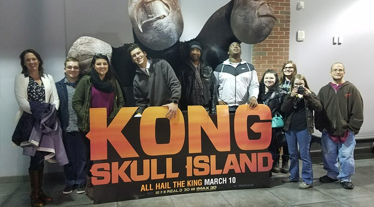 Delaware Tech Introduction to Film students pose with a giant King Kong hand in the lobby of the Penn Cinema Riverfront prior to touring the facility.