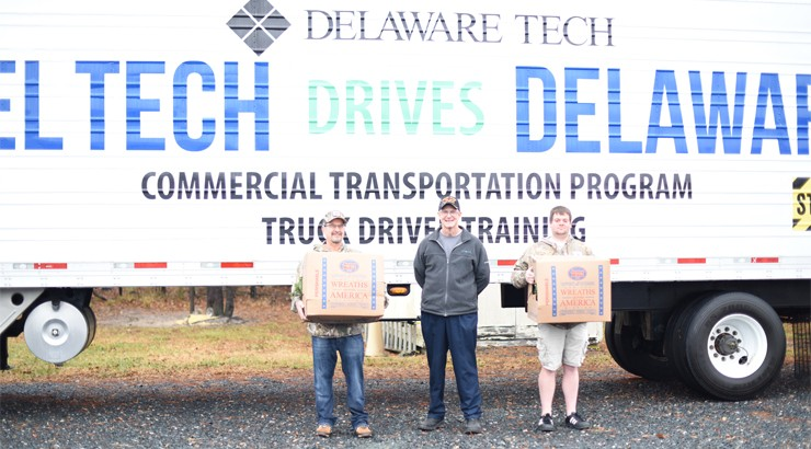 Three people standing beside a tractor trailer holding wreaths