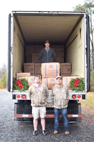 Three people at the back of a tractor-trailer, one standing inside the trailer and two standing on the ground