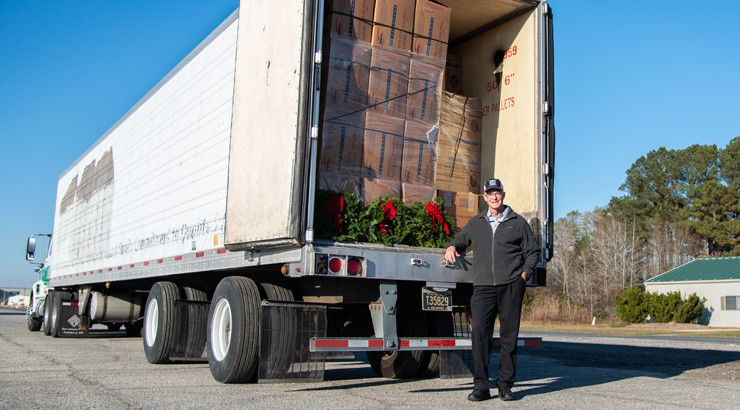 Bryan Ward standing beside a tractor trailer full of wreaths
