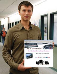 Student holding image of web design comp