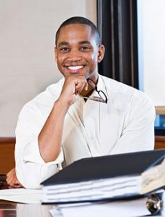 Male Business Administration student at desk smiling.
