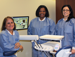 Three dental services team members smiling