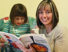 Female paraeducator student with toddler in classroom reading book