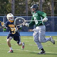 Delaware Tech lacrosse player running with the ball.