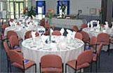 Catered tables set for dinner with white table cloths
