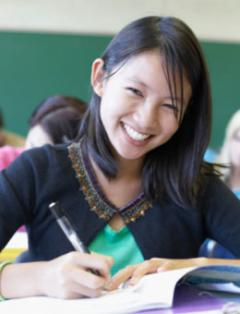 Smiling female student writing a paper