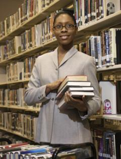 Female student holding books in library
