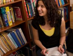Student sitting in library smiling with paper and pen